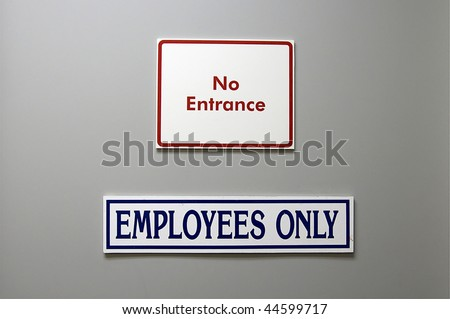 Red and Blue trimmed entrance signs warning not to enter on a gray door - stock photo
