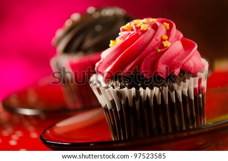 red and brown cupcakes on red background - stock photo