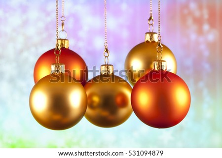 Red and gold baubles on abstract colored background