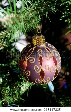 Red and gold Christmas ball ornament hangs on a tree - stock photo