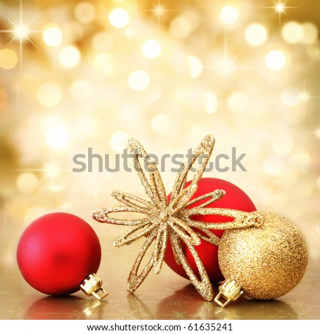 Red and gold Christmas baubles and star on background of defocused golden lights. Shallow DOF. - stock photo