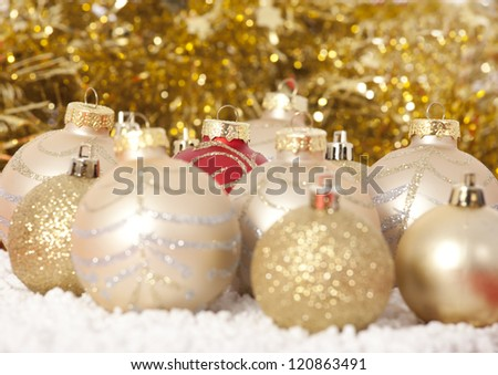 Red and gold Christmas baubles on background of with golden lights