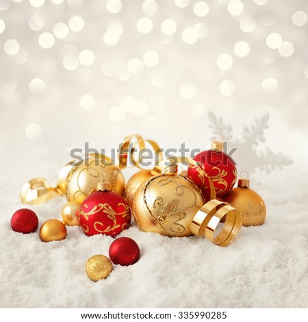red and gold christmas ornaments in the snow