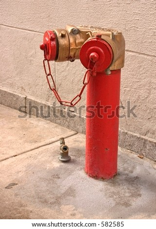 Red and gold fire hydrant sprinkler connection for a building in New York City. - stock photo
