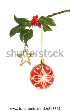 Red and gold glitter Christmas bauble and star hanging from a holly branch isolated against white