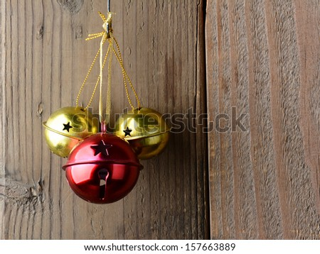Red and Gold Jingle Bells hanging on a rustic wooden wall.  - stock photo