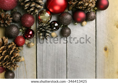 Red and gold sparkly christmas tree bulb decorations, pine cones, and acorns frame a background of weathered old barn wood. - stock photo