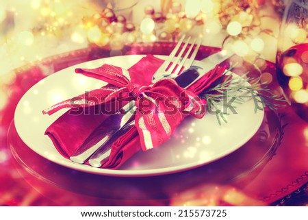 Red and gold themed holiday dinner table plate setting - stock photo