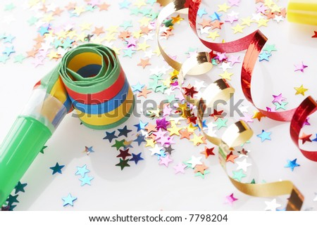 red and golden spirals, small confetti stars and colorful blower on white background, party time