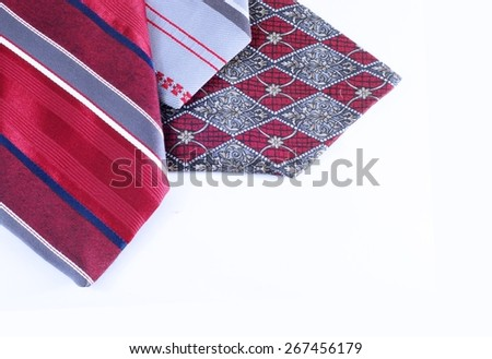 Red and gray neckties crisscrossing each other isolated on white. Horizontal image good for father's day, textile, clothing or fashion. Copy space in lower right corner. Prominent tie is striped.  - stock photo