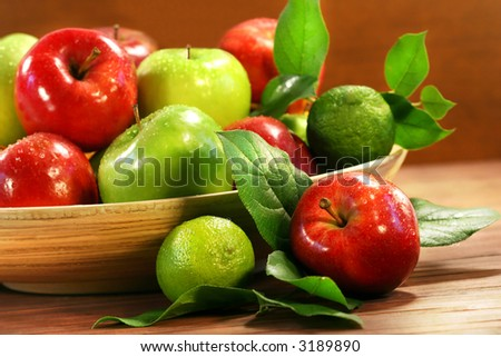 Red and green apples in a wooden bowl - stock photo