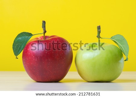 Red and green apples on yellow background