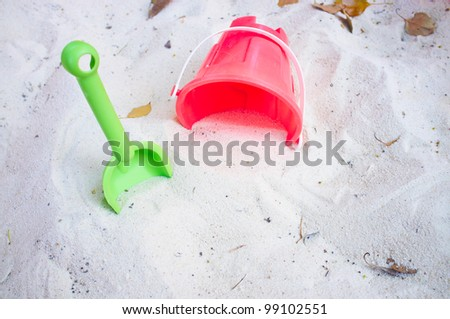 Red and green beach toys in sand - stock photo