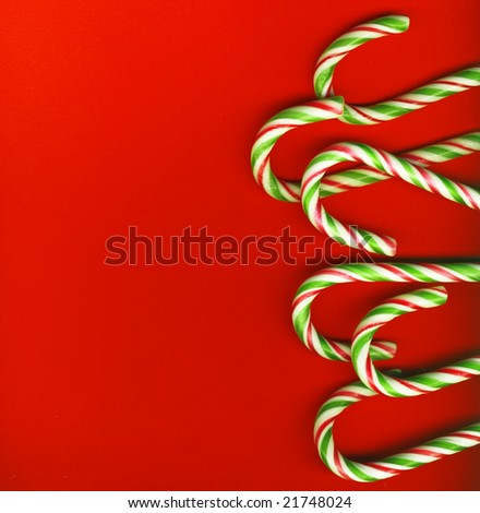 red and green Christmas candy canes isolated on red - stock photo