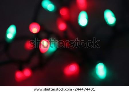 Red and green Christmas light string shot blurred on a black background.  - stock photo