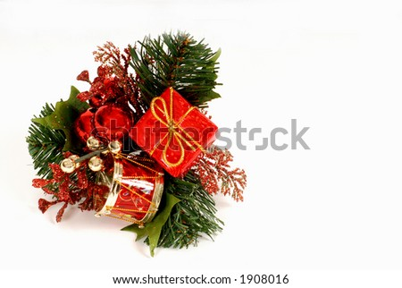 Red and green Christmas ornament made of small drum, wrapped package, red and gold balls and pine isolated on white