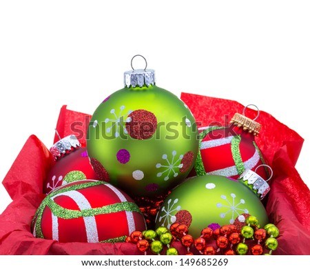 Red and green Christmas ornaments in a box with copy space isolated on white  - stock photo