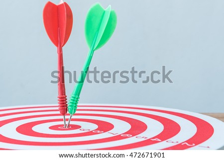 red and green darts hit on center of dartboard