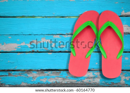 red and green flip flop sandals on blue wood - stock photo