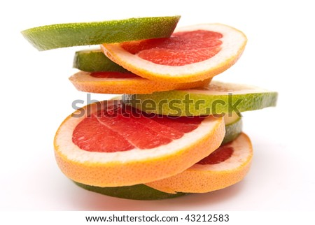 red and green grapefruit parts tower isolated on white background