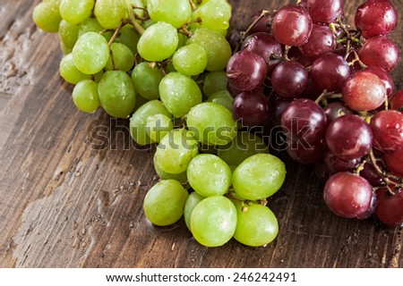 Red and green grapes wet from washing on a vintage distressed cherry wood table - stock photo