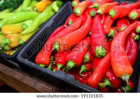 Red and green hot chillies on display at the market. - stock photo