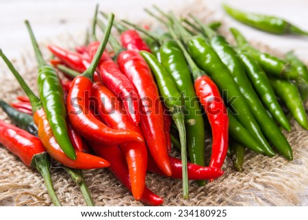 Red and green hot pepper on burlap - stock photo