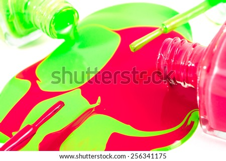 Red and green nail polish bottles with nail polish pouring from them on the white background - stock photo