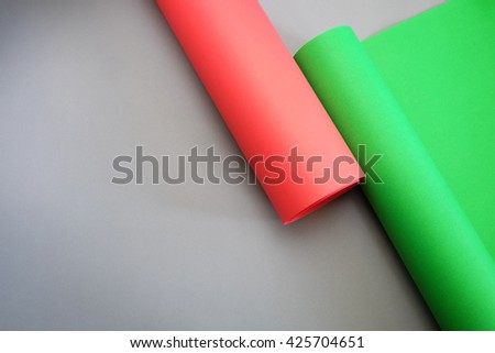 red and green paper roll on grey paper background,copy space - stock photo