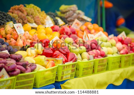 Red and green paprika peppers and apples, pears, oranges, pomegranate on back on city market - stock photo