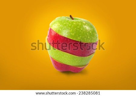 Red and green sliced apple on orange background. - stock photo