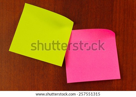 Red and green stickers on a wooden board from notice - stock photo