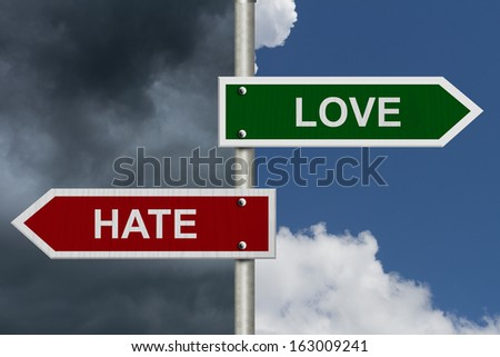 Red and green street signs with blue and stormy sky with words Love and Hate, Love versus Hate