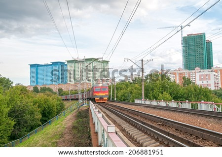 Red and grey suburban electric train moves towards on railroad turn vanishing against skyline background. Moscow, Russia.