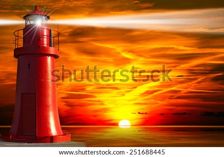 Red and metallic lighthouse with light beam at sunset with clouds