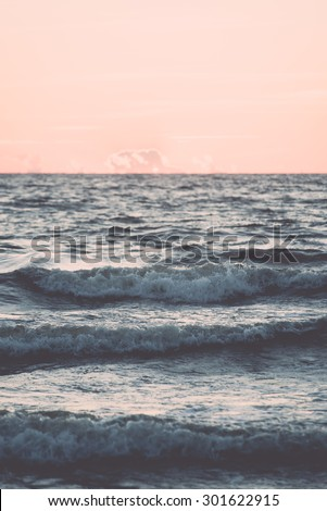 red and orange dramatic sunset on the sea beach with colorful sky and waves crushing on the shore- vintage retro effect - stock photo