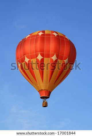 Red and orange hot air balloon in the blue sky. - stock photo