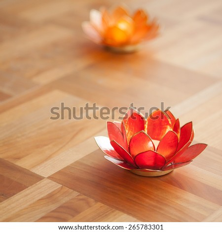 Red and orange lotus candles on wooden floor - stock photo