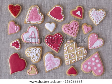 Red and pink heart cookies on a grey fabric background - stock photo