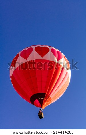 Red and pink heart hot air balloon with bright blue sky taking off at balloon festival - stock photo