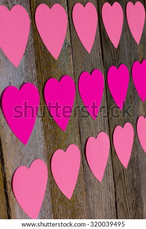 Red and pink paper hearts for messages on old wooden boards, selective focus. Copy space. Free space for text - stock photo