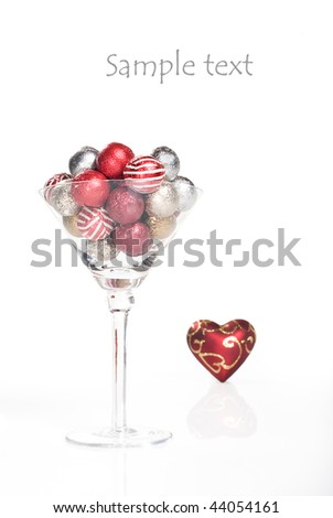 Red and silver chocolate balls in a martini glass with a red heart on white background with space for text - stock photo