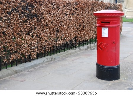 red and vintage british postbox on the sidewalk - stock photo