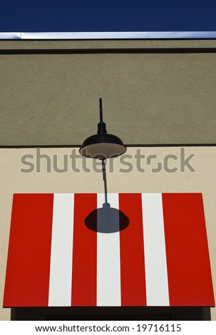 Red and white awning with black street lamp