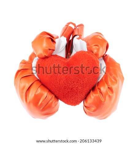 Red and white boxing gloves holding the red plush toy heart, isolated over the white background - stock photo