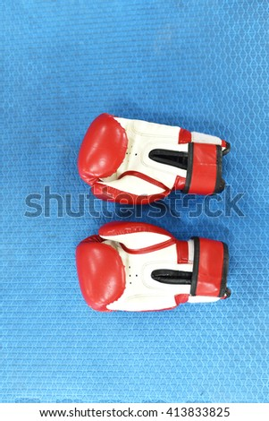 red and white boxing gloves or martial arts gear on a blue background - stock photo