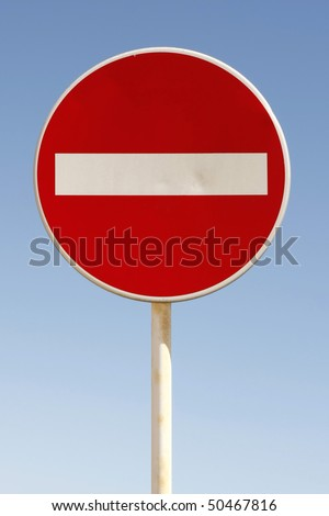 Red and white british no entry road sign with a blue sky - stock photo