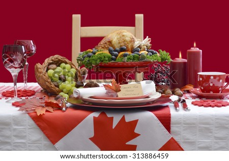 Red and white Canadian theme Thanksgiving Table setting with flag and Roast Turkey Chicken on large platter centerpiece .  - stock photo