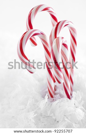 Red and white candy canes surrounded by faux snowflakes against a white background. - stock photo