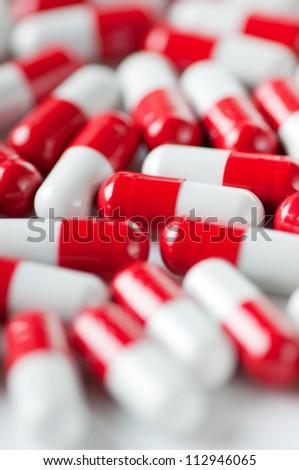 Red and white capsules, macro, vertical shot - stock photo
